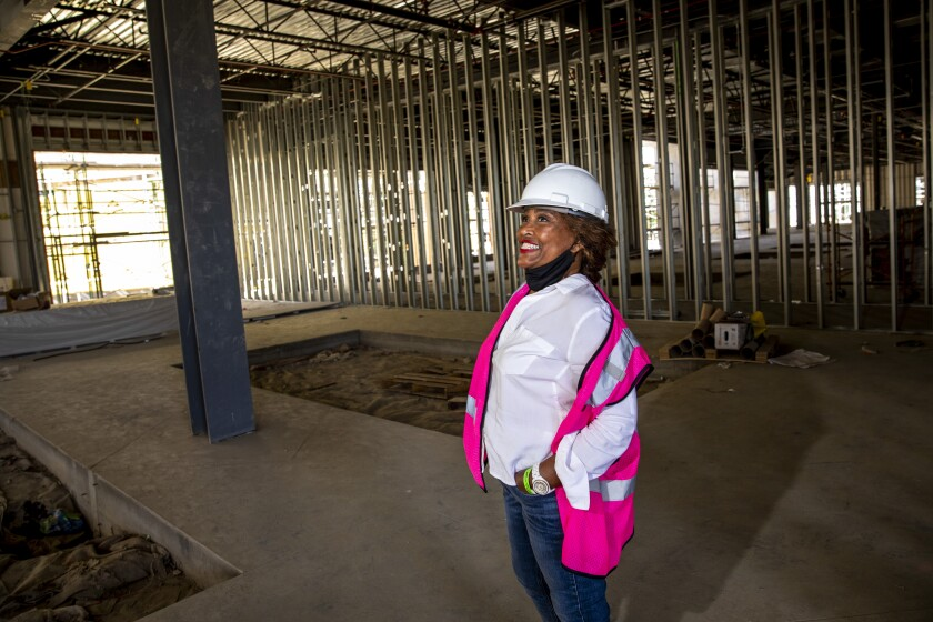 A woman wearing a hard hat smiles while standing in a building under construction.