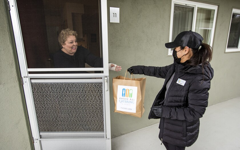 Valery Moreno delivers meals for Meals on Wheels Orange County to Lillian Modzeleski on March 3.