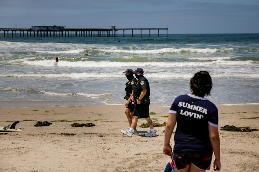 Two San Diego Police Department officers patrol along Ocean Beach ahead of Memorial Day Weekend on May 22, 2020 in San Diego, California.
