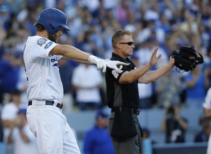 El lanzador de los Dodgers Clayton Kershaw (i) celebra tras marcar en un RBI doble de Justin Turner durante la séptima entrada del juego cinco de la Serie de Campeonato de la Liga Nacional. EFE