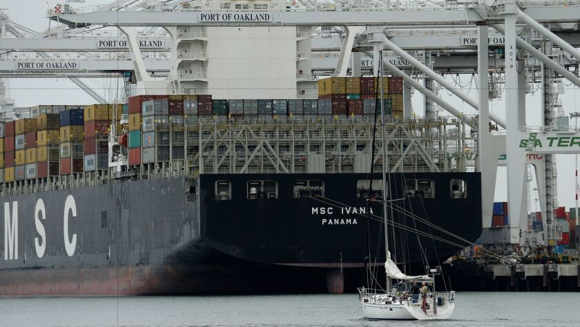 A sailboat makes its way past the container ship MSC Ivana as it is unloaded at the Port of Oakland in March.