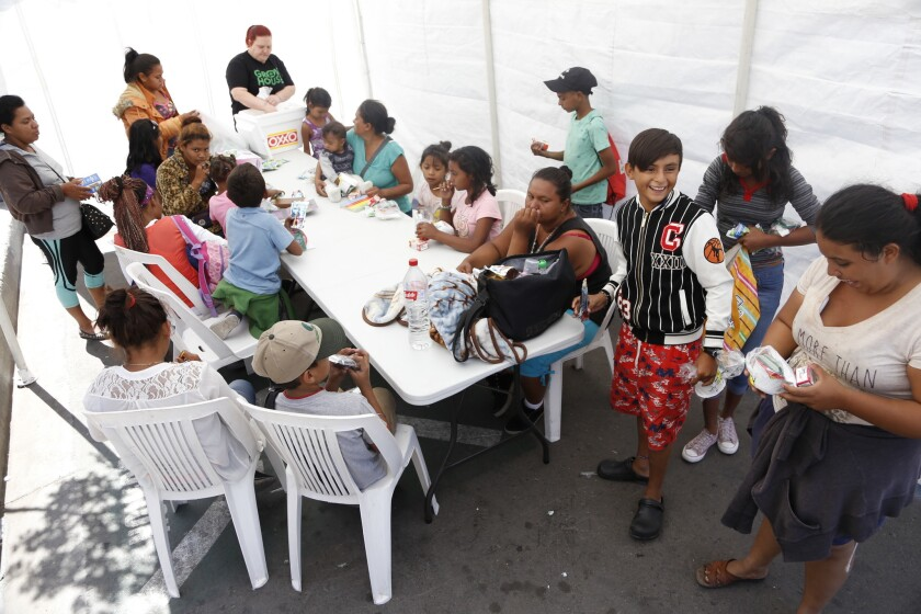 Migrants staying at a shelter in Tijuana's Zona Norte gather for lunch on Friday.