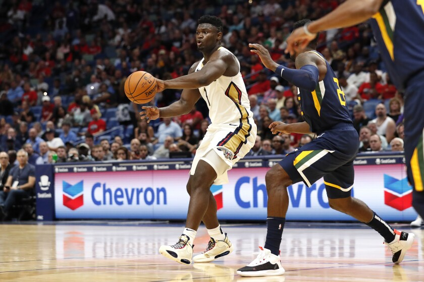 New Orleans Pelicans forward Zion Williamson (1) drives past Utah Jazz forward Jeff Green (22) during the first half of a preseason NBA basketball game in New Orleans, Friday, Oct. 11, 2019. (AP Photo/Tyler Kaufman)