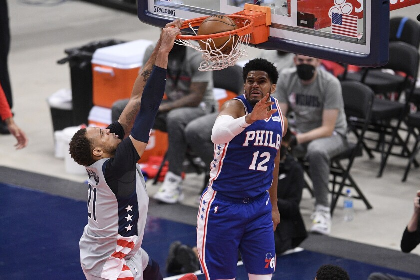 Washington Wizards center Daniel Gafford (21) dunks against Philadelphia 76ers forward Tobias Harris (12) during the second half of Game 4 in a first-round NBA basketball playoff series, Monday, May 31, 2021, in Washington. (AP Photo/Nick Wass)