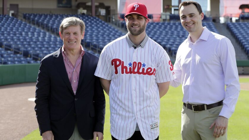 Bryce Harper, center, poses for a photo with Philadelphia Phillies managing partner John Middleton, left, and general manager Matthew Klentak after being introduced as a Phillies player during a news conference Saturday.