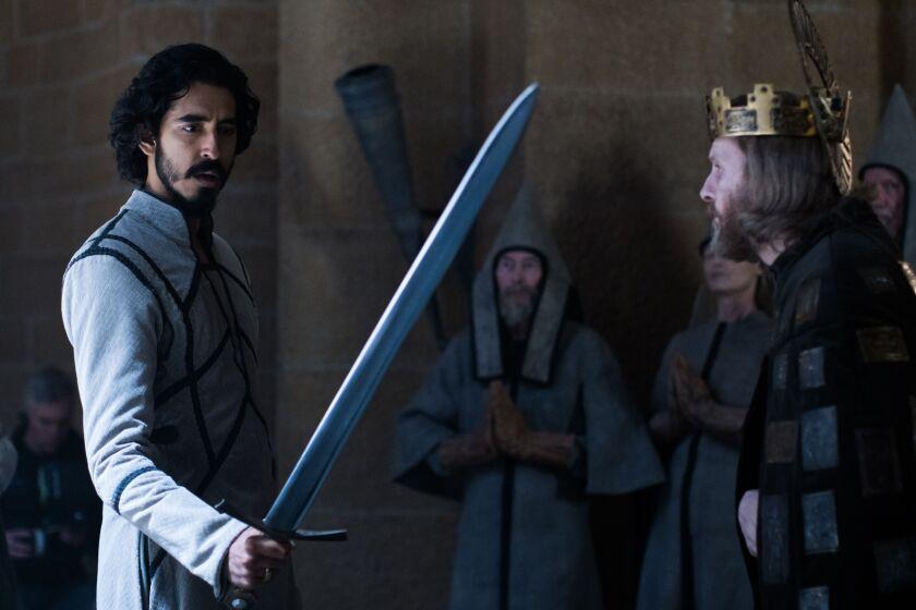"Sean Harris as King Arthur and Dev Patel as Gawain holding a sword in ""The Green Knight"""