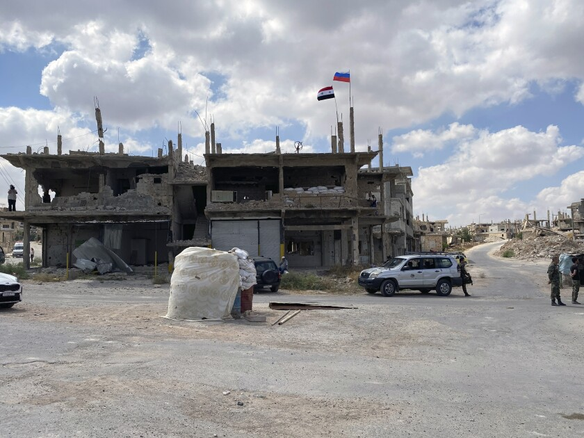 Syrian soldiers stand guard near a damaged building in the southern city of Daraa, Syria, Sunday, Sept 12, 2021. A Russian-negotiated deal went into effect last week to end a government siege and intense fighting in the city of Daraa and with rebel fighters holed up Daraa al-Balad forcing some of them to go to the rebel-held north and others to surrender their weapons in return for amnesty. (AP Photo)
