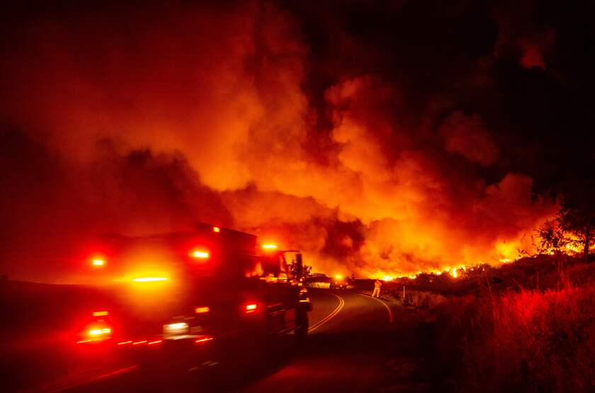 A firetruck heads toward flames during the Kincade fire near Geyserville, Calif., on Oct. 24. The fire broke out in spite of rolling blackouts by utility companies in both Northern and Southern California.