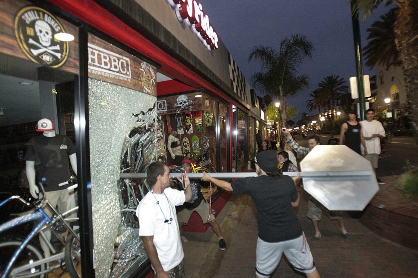 A rioter smashes a stop sign through the windows of a bike shop at Main and Orange Streets in downtown Huntington Beach on Sunday.