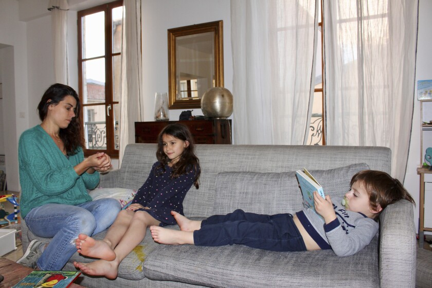 Mathilde Manaud plays on a sofa with her children Mila, 7, and Andre, 3, in Paris on April 30. Many French parents are deeply torn over whether to send their children to school when they reopen starting Monday.