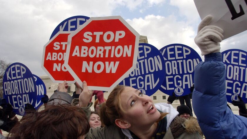Pro–life demonstrators stand in front of pro–choice counter–demonstrators to block their signs in fr