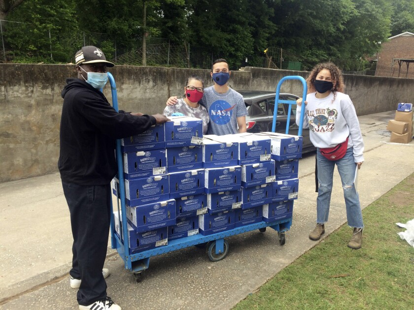 In this photo provided by Repair the World, Serve the Moment volunteers distribute produce boxes in May 2020. (Courtesy of Repair the World via AP)