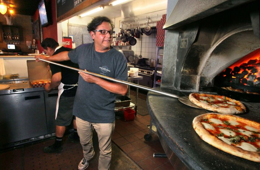 Hector Reyna places a pizza in the oven at Privateer Coal Fire Pizza. He and business partner Charlie Anderson are the founders and owners of the South Oceanside business. They don't want to owe anyone any money or take on new partners.