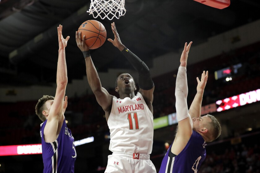 Maryland guard Darryl Morsell (11) goes up for a shot against Holy Cross forward Connor Niego, left, and guard Austin Butler during the first half of an NCAA college basketball game, Tuesday, Nov. 5, 2019, in College Park, Md. (AP Photo/Julio Cortez)