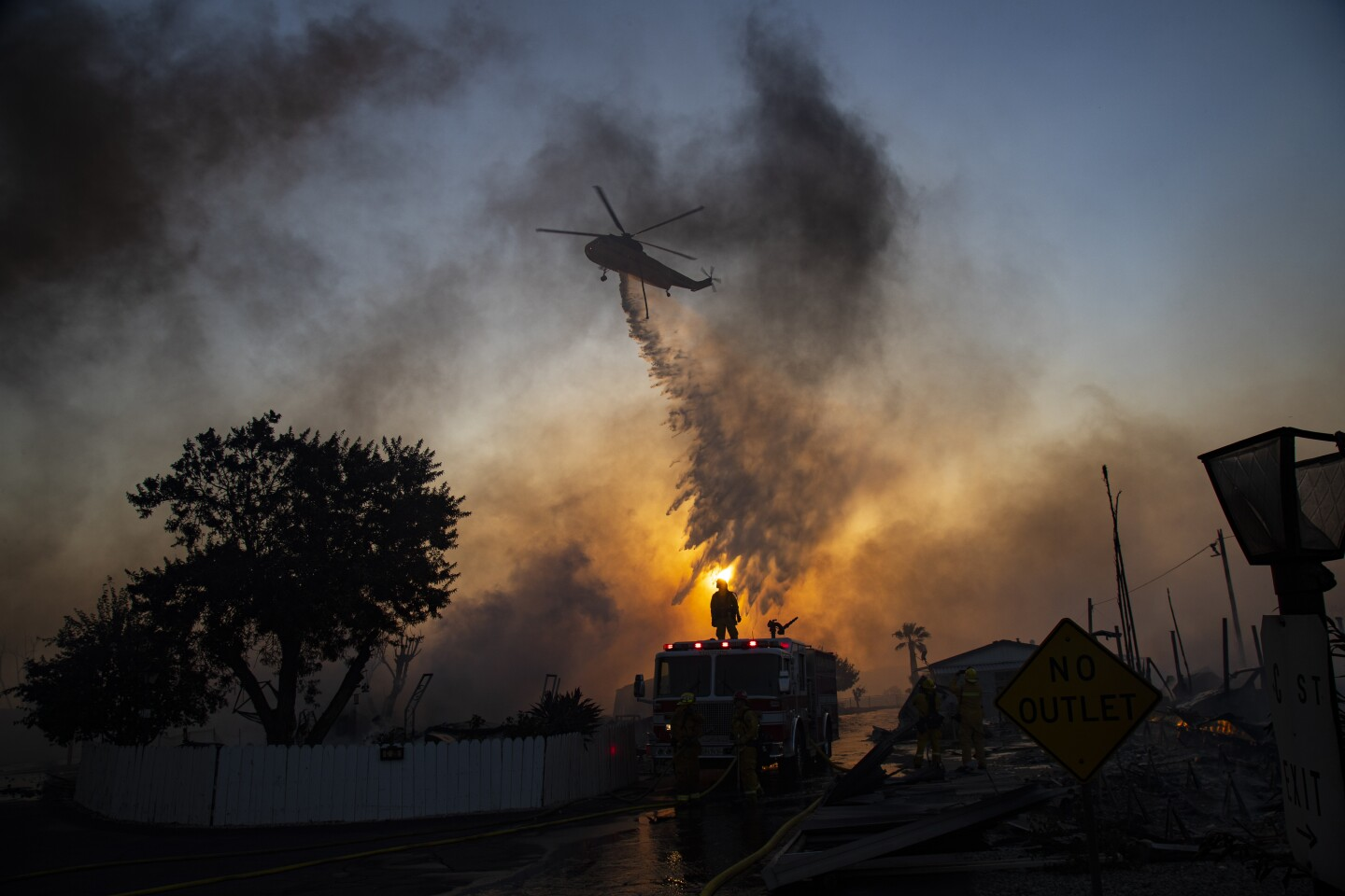 CALIMESA, CA - OCTOBER 10, 2019: A water dropping helicopter drops water on burning mobile homes to try and keep the Sandalwood fire from spreading at Villa Calimesa mobile home park on October 10, 2019 in Calimesa, California. Multiple mobile homes were lost in the fire.(Gina Ferazzi/Los AngelesTimes)