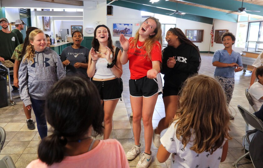 Experience Camp participant Carrie Fleming, 16, of South Pasadena, tall middle, leads joke telling among fellow campers in the dining hall at Green Oak Ranch after lunch.