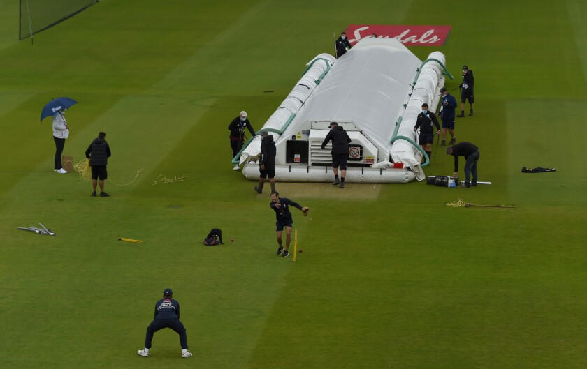 Groundsmen cover the pitch area before the start of the first day of the 1st cricket Test match between England and West Indies, at the Ageas Bowl in Southampton, England, Wednesday July 8, 2020. (Mike Hewitt/Pool via AP)