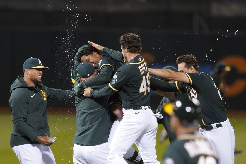 Oakland Athletics' Elvis Andrus, third from left, is congratulated by teammates after hitting a single to score Matt Chapman during the ninth inning of a baseball game against the Kansas City Royals in Oakland, Calif., Friday, June 11, 2021. (AP Photo/Jeff Chiu)