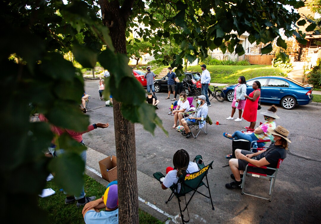 Alicia Smith leads a community meeting in the street outside the home of a Minneapolis City Council member.