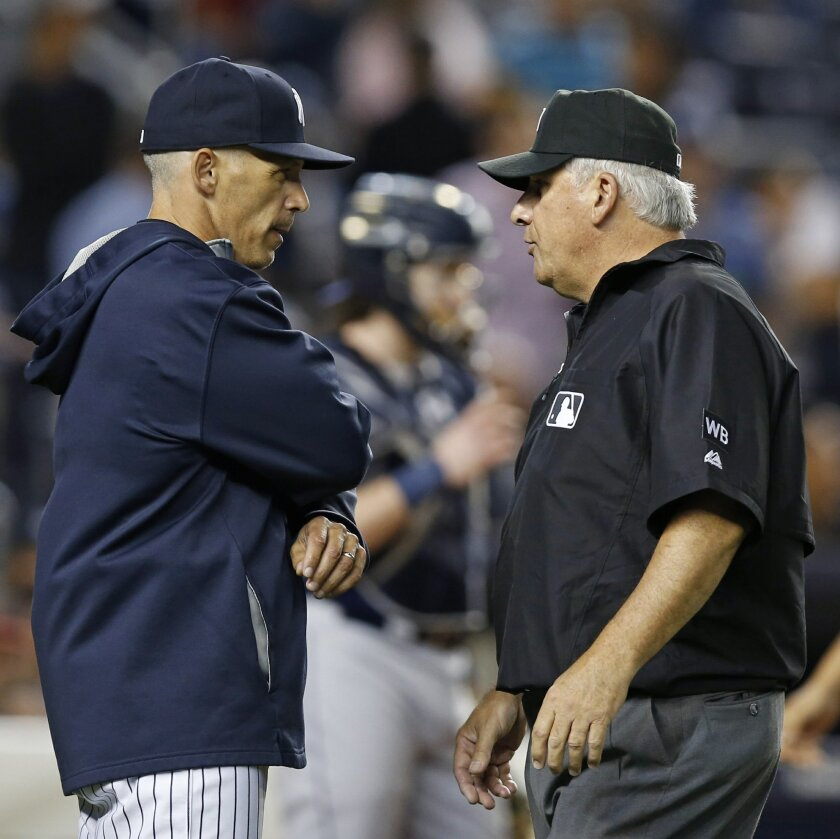 New York Yankees manager Joe Girardi, left, confers with umpire crew chief Larry Vanover after a video review of Yankees' Stephen Drew sliding home upheld the call on the field during the Yankees' 4-3 loss to the Tampa Bay Rays in a baseball game at Yankee Stadium in New York, Tuesday, Sept. 9, 2014. Left fielder Matt Joyce threw out Drew in the fifth inning to preserve the Rays' one-run lead. Rays catcher Ryan Hanigan is at rear between Girardi and Vanover. (AP Photo/Kathy Willens)