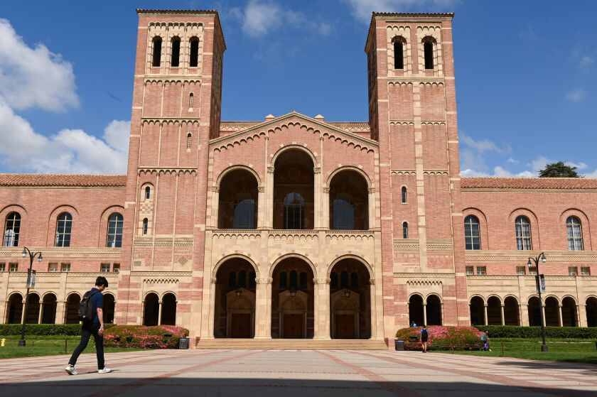 A student walks toward Royce Hall on the campus of University of California at Los Angeles