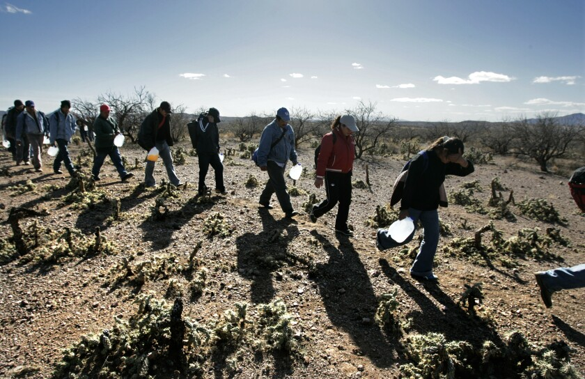 Lugging gallon jugs of water, migrants walk along footpaths just north of the Mexico-Arizona border in 2007.
