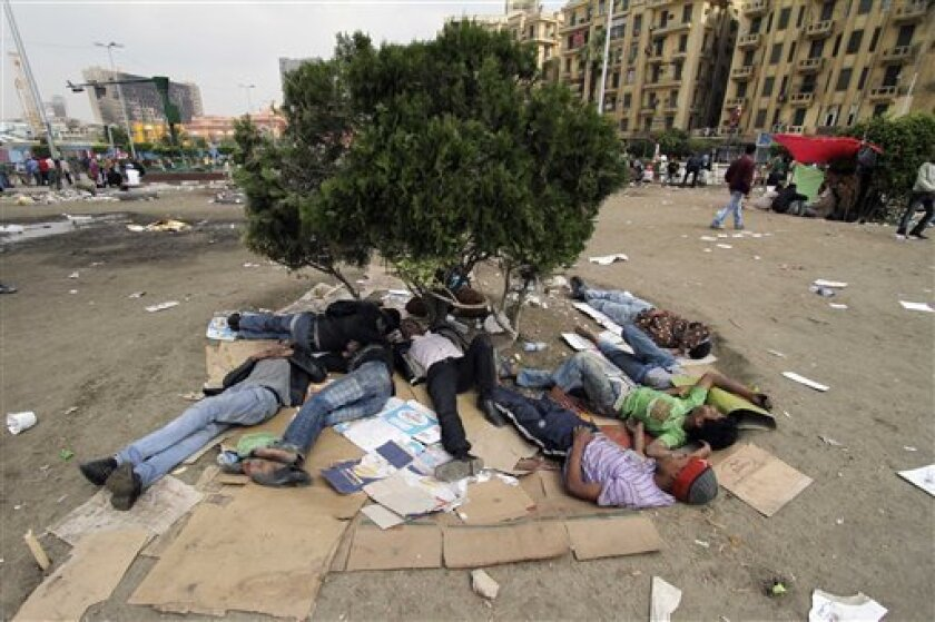 Protesters sleep on cardboard following an attack by security forces in Tahrir Square, in Cairo, Egypt, Saturday, April 9, 2011. Demonstrators burned cars and barricaded themselves with barbed wire inside a central Cairo square demanding the resignation of the military's head after troops violently dispersed an overnight protest killing one and injuring scores. (AP Photo/Khalil Hamra)
