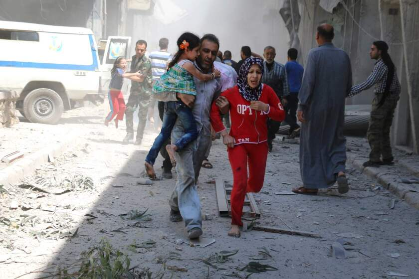 A Syrian family runs for cover following a reported airstrike April 29 on a rebel-held neighbourhood of Aleppo.
