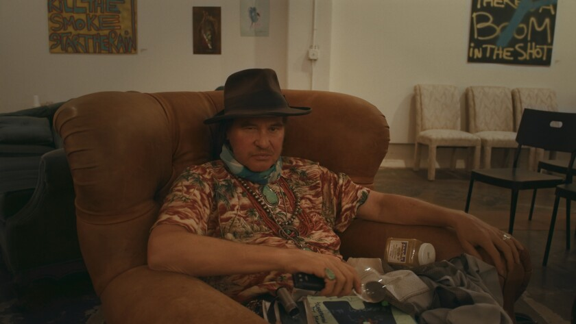Val Kilmer, wearing a hat and a scarf, sits in a chair