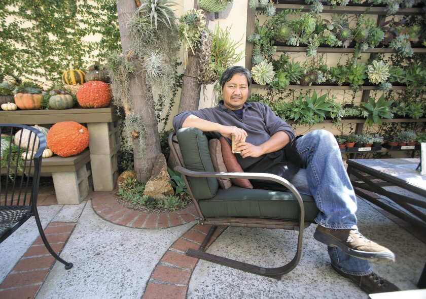 "Peter Loyola relaxes amid the many plantings in The Succulent Cafe, at 322 N. Cleveland St. in Oceanside. When combining succulents with containers, Loyola says, ""I go on autopilot."""