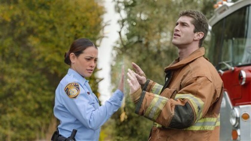 """This publicity image released by CBS shows Natalie Martinez, left, and her Josh Carter in a scene from the series """"Under the Dome,"""" about a small town that is suddenly and inexplicably sealed off from the rest of the world by a massive transparent dome. The Nielsen company says an estimated 13.5 million people watched the debut last week. More than 3 million watched on their DVRs or through on-demand services, and CBS reran the premiere Sunday, which drew another 5.1 million viewers. A second ep"""