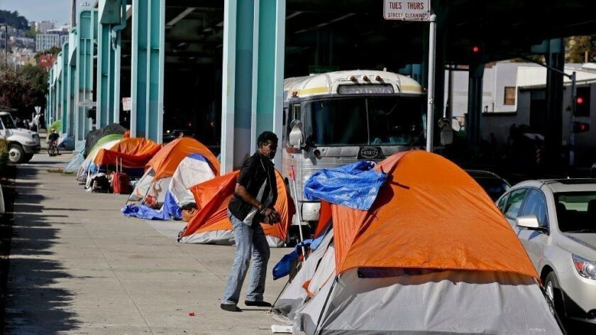 A man stands outside his tent on Division Street in San Francisco in 2016. San Francisco struggles with income inequality. A survey from the Pew Research Center shows Republicans and Democrats hold increasingly divergent views on the economy.