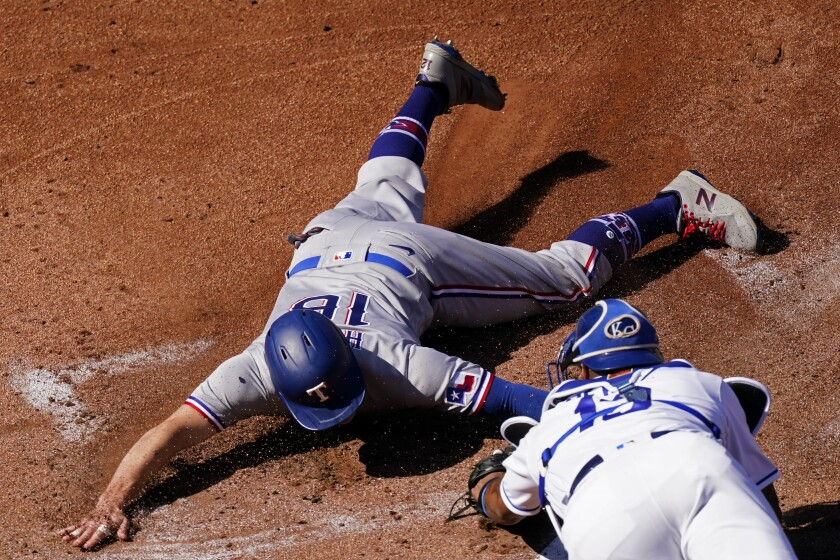 Texas Rangers' Brock Holt (16) is tagged out by Kansas City Royals catcher Salvador Perez trying to score on a single by Jose Trevino during the first inning of a baseball game Thursday, April 1, 2021, in Kansas City, Mo. (AP Photo/Charlie Riedel)