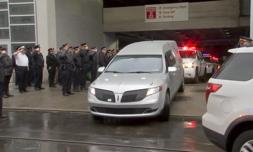 In this image provided by WPVI-TV 6ABC, police officers salute as the hearse carrying the body of Philadelphia police officer Cpl. James O'Çonnor leaves the hospital on Friday, March 13, 2020 in Philadelphia. O'Çonnor was shot and killed early Friday as he served a homicide warrant at a home in the city's Frankford section. (WPVI-TV 6ABC via AP)
