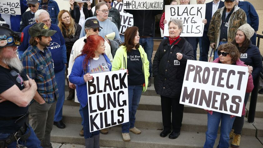 Coal mining advocates listen as Patty Amburgey, of Letcher, Ky., speaks about the death of her husba