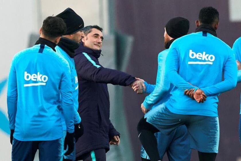 El entrenador del Barcelona Ernesto Valverde (3i) saluda al argentino Lionel Messi durante el entrenamiento del equipo en la víspera del partido de liga que les enfrenta mañana al Athletic de Bilbao en San Mamés. EFE