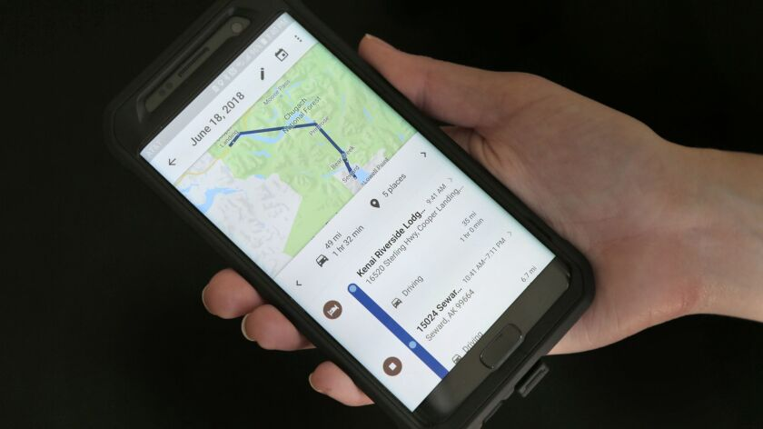 FILE- In this Aug. 8, 2018, file photo a mobile phone displays a user's travels using Google Maps in