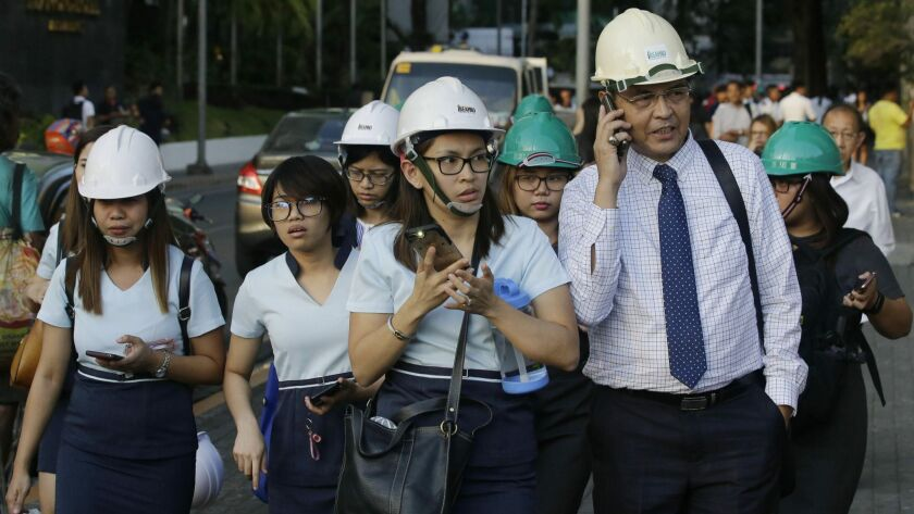 Wearing helmets, employees evacuate their building following an earthquake in Manila, Philippines Mo