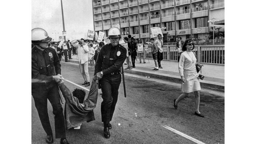 June 23, 1967: An antiwar protester is removed by LAPD officers at Century Plaza Hotel.