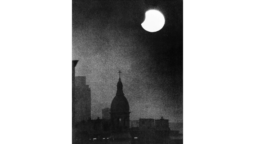 The partial solar eclipse is visible through fog on Dec. 13, 1974. In the foreground is St. Vibiana's Cathedral at Main and 2nd streets in downtown L.A. This photo was published on Page 1 of the Dec. 14, 1974 Los Angeles Times.