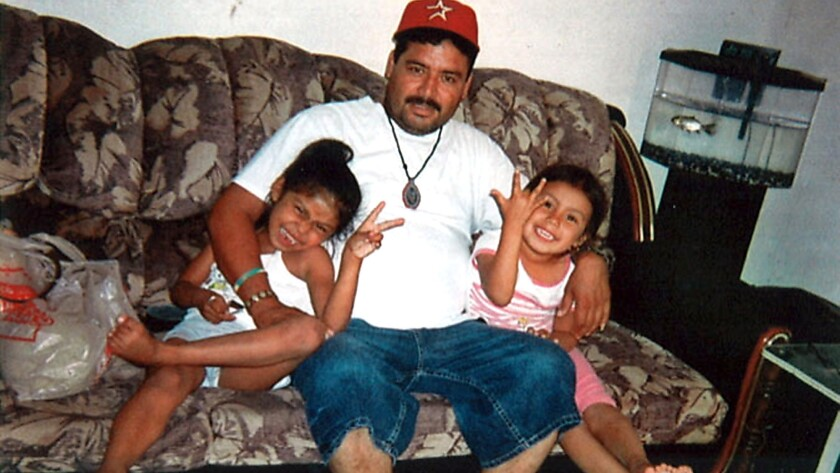 Guillermo Arevalo Pedraza sits with his daughters, Priscila, left, and Mariana. When he died, they were 10 and 9, respectively.