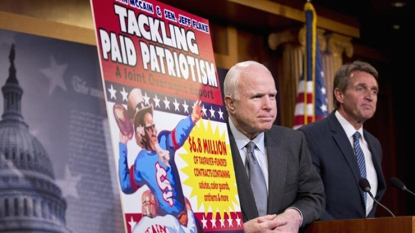 """Sens. John McCain, left, and Jeff Flake, Republicans from Arizona, talk about """"paid patriotism"""" during a news conference in Washington on Wednesday. The senator detailed evidence in a report of the Pentagon paying pro teams to honor soldiers at games."""