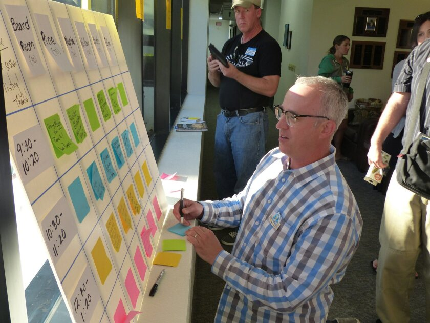 """David Theriault, a teacher from Fountain Valley High School, checks out the sessions board at EdCamp on Saturday at the Escondido Union School District headquarters. EdCamp is a free """"unconference"""" for teachers."""