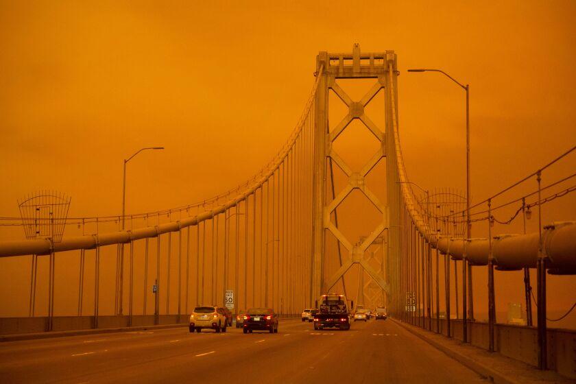 Cars drive along the San Francisco Bay Bridge under an orange smoke-filled sky
