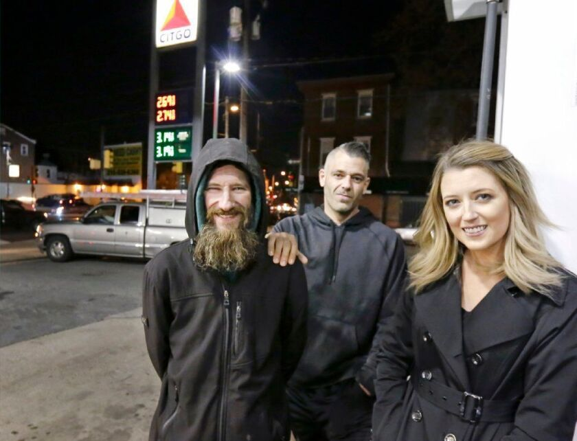 In this Nov. 17, 2017, photo, Johnny Bobbitt Jr., left, Kate McClure, right, and McClure's boyfriend Mark D'Amico pose at a Citgo station in Philadelphia. McClure and D'Amico later raised more than $400,000 for Bobbitt