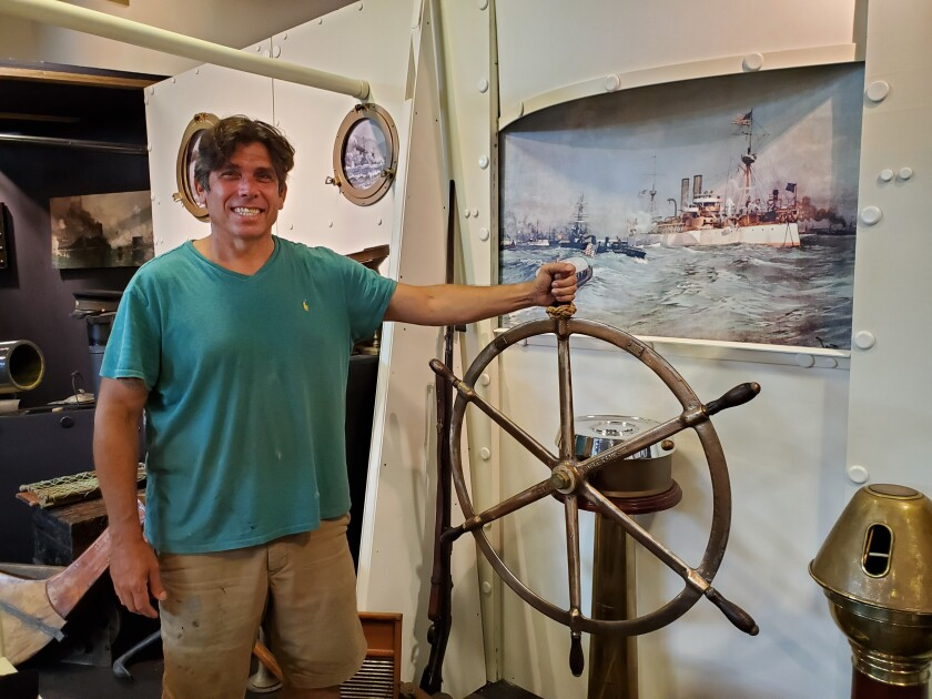 """""""Permission to Come Aboard"""" curator Joe Frangiosa Jr. stands in his in-development Spanish-American War ship booth."""