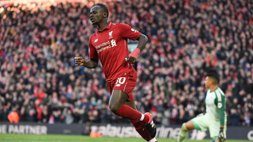 Liverpool striker Sadio Mane trots back to midfield after scoring a goal against Cardiff City last weekend.