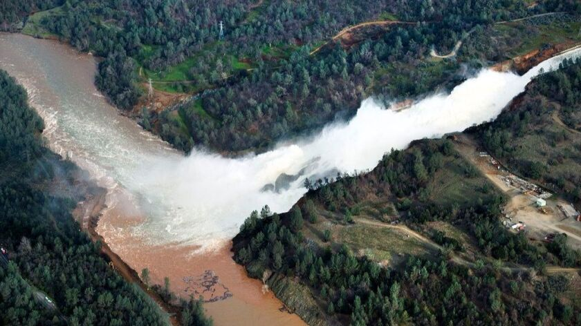 Water continues to run down the main spillway at Lake Oroville on Monday in Oroville. The water level dropped Monday behind the nation's tallest dam.