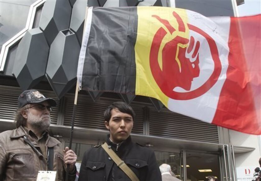 A French supporter of the Indian cause, who refused to give his name, left, holds a flag of the American Indian Movement and an American exchange student, member of the Arizona's Hopi tribe, Bo Lomahquahu, right, stand outside of the Druout's auction house to protest the auction of Native American Hopi tribe masks in Paris, Friday, April 12, 2013. A contested auction of dozens of Native American tribal masks went ahead Friday afternoon following a Paris court ruling, in spite of appeals for a de
