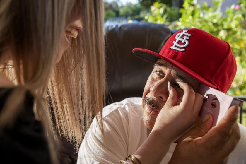 Wendy Rangel puts fake eyelashes on her dad, Genaro Rangel, before filming him on TikTok.